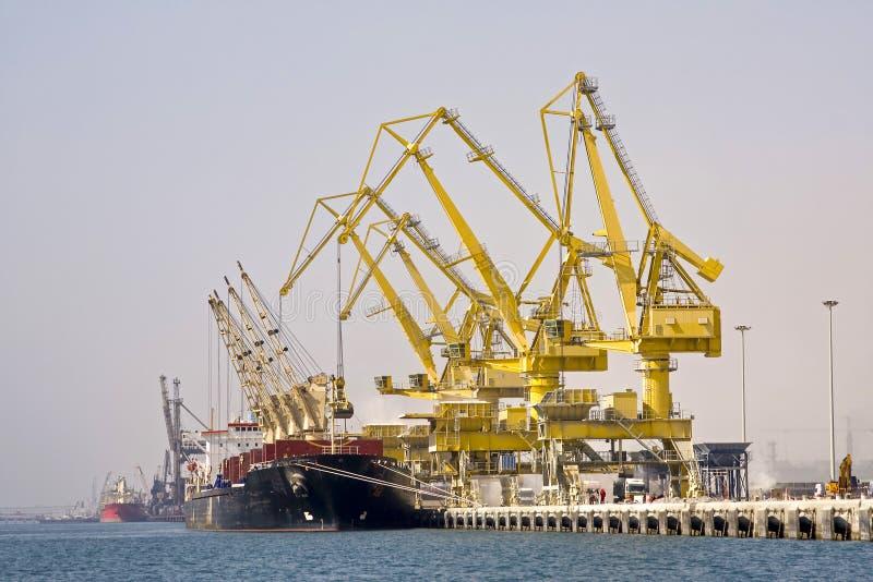 Bulk cargo ship under port crane bridge. royalty free stock image
