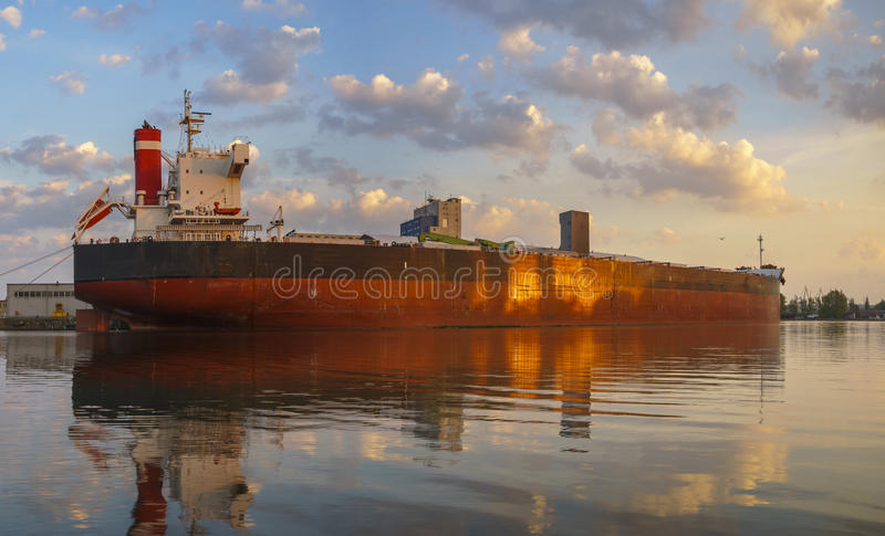 Bulk carrier moored at the quay, and busy with cargo operations. stock photography