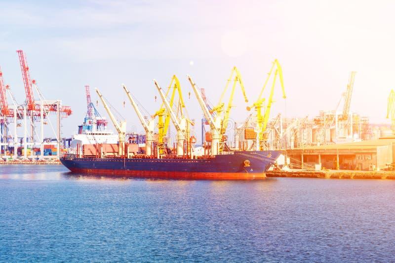 Bulk carrier ship in the port on loading. Bulk cargo ship under port crane bridge. royalty free stock photos