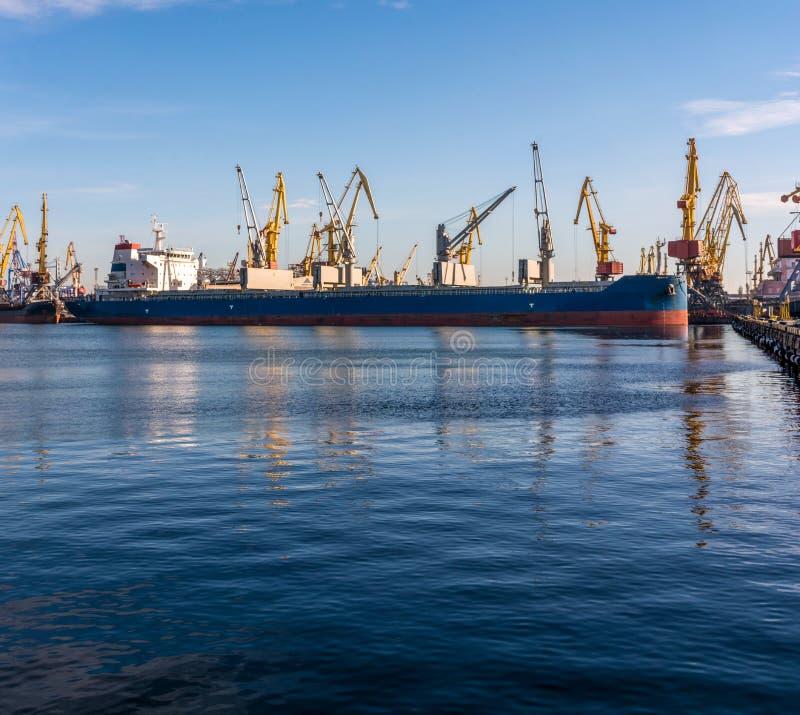 Bulk carrier ship in the port on loading. Bulk cargo ship under port crane bridge. Ship in seaport at sunset royalty free stock images