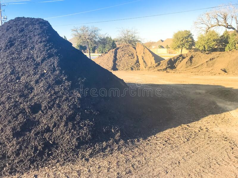 Bulk compost wholesale plant near highway with pile of organic matters near Dallas, Texas. Wholesale compost near highway with large pile of compost, mulch, sand royalty free stock photography