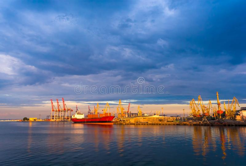 Bulker in port. Loading on the ship. Sea. Sunset. Beautiful clouds. Calm sea. International transportation of goods. Port cranes. royalty free stock image