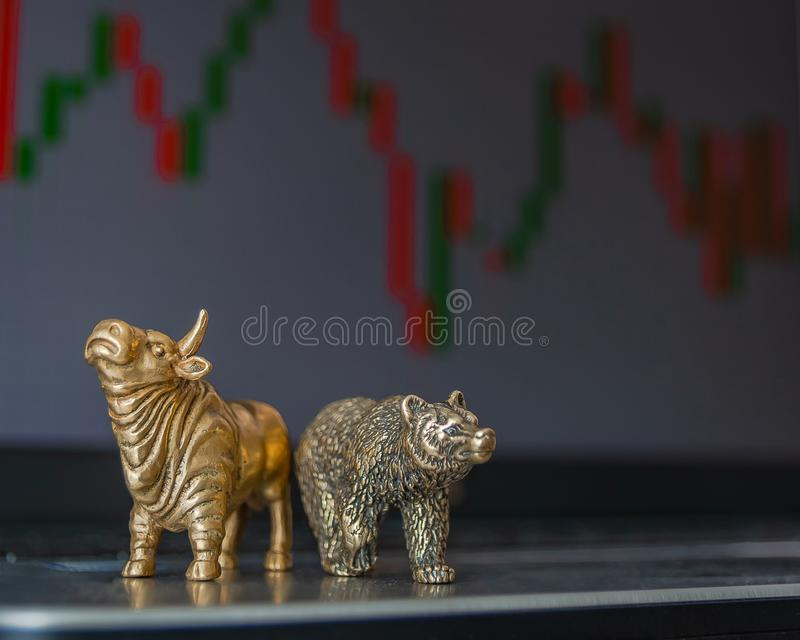 Symbols of stock trading on the background of the trading chart. Bull and bear as symbols of stock trading on a blurred background of price graphics. The stock images