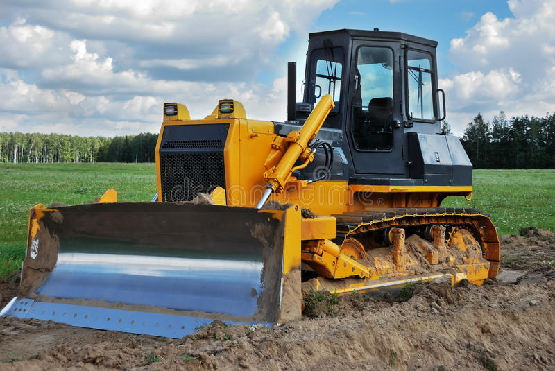 Bulldozer. Standing outdoor in green field stock images