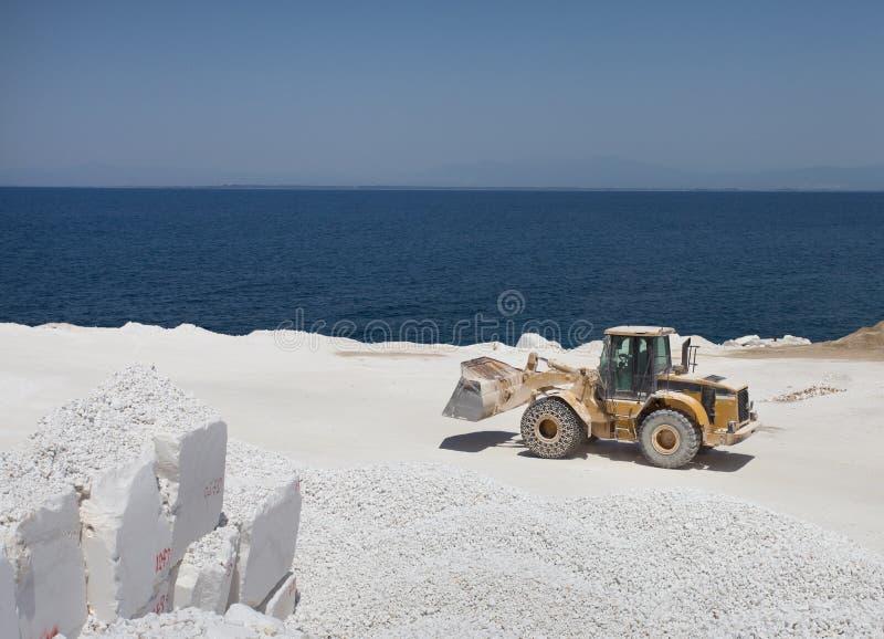 Bulldozer bij marmeren steengroeve op eiland stock foto's