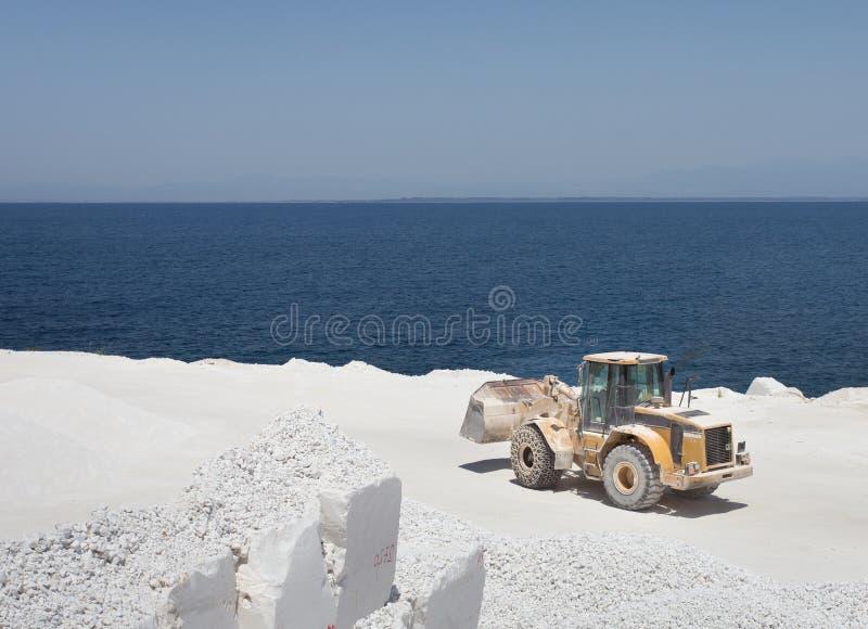 Bulldozer bij marmeren steengroeve op eiland stock afbeelding