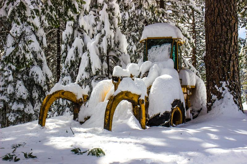 Bulldozer Covered In Wet Winter Snow. Bulldozer Buried In Heavy Wet Winter Snow Amidst Tree In Mountains stock images