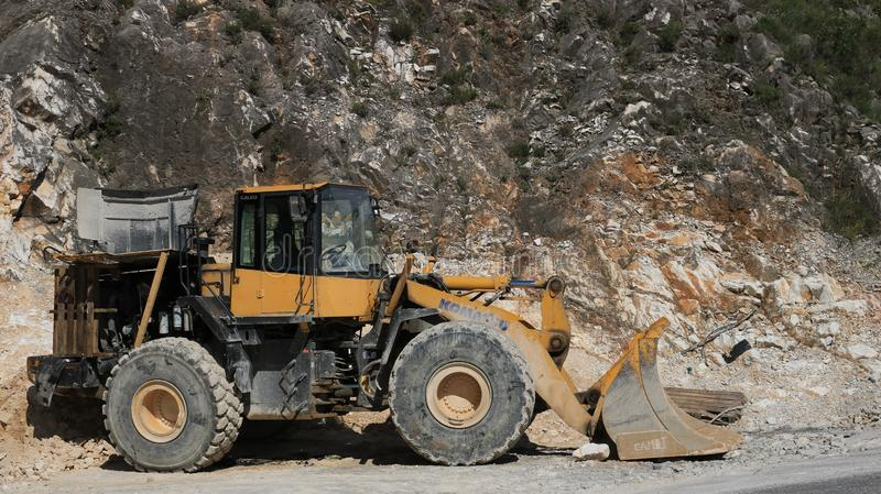Bulldozer in a Carrara marble quarry. A large Komatsu mechanical stock image