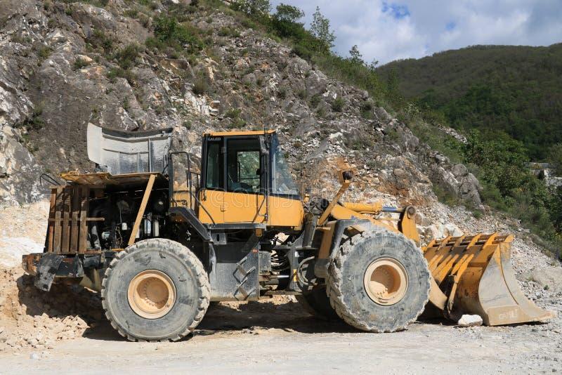 Bulldozer in a Carrara marble quarry. A large Komatsu mechanical royalty free stock photos