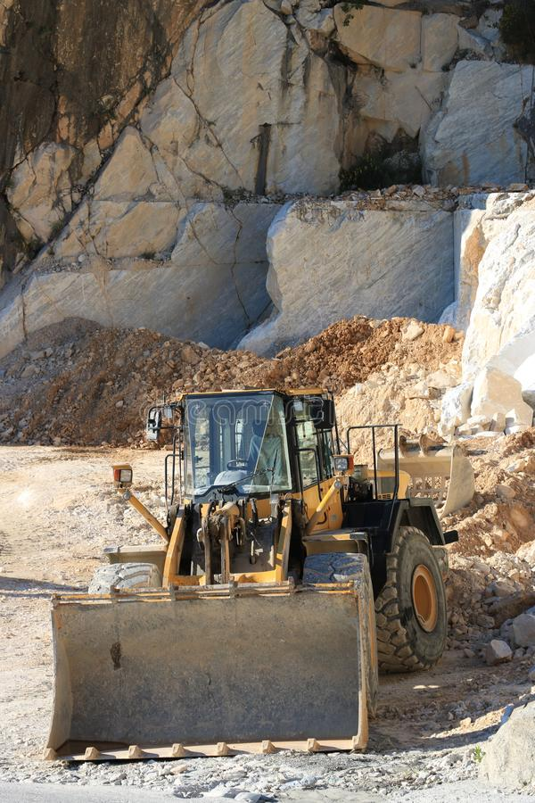 Bulldozer in a Carrara marble quarry. A large mechanical shovel stock images
