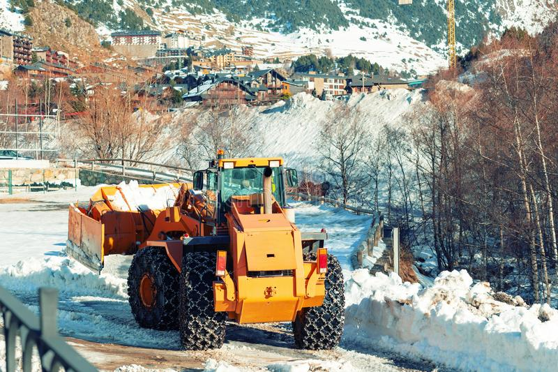 A bulldozer with chains on wheels removes snow in a village in the mountains of Andorra. stock photos