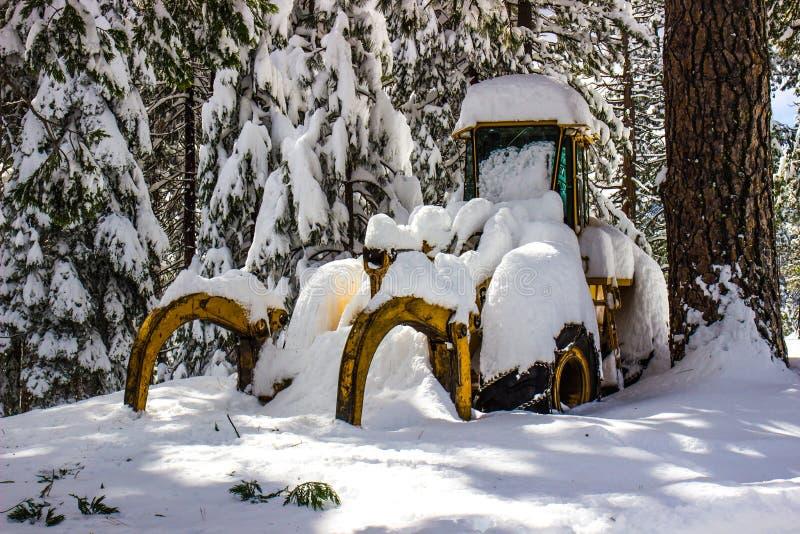 Bulldozer coperto nella neve bagnata di inverno immagini stock
