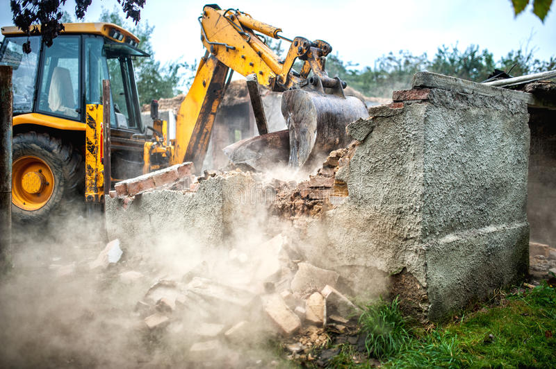 Bulldozer demolishing concrete brick walls of small building stock photo