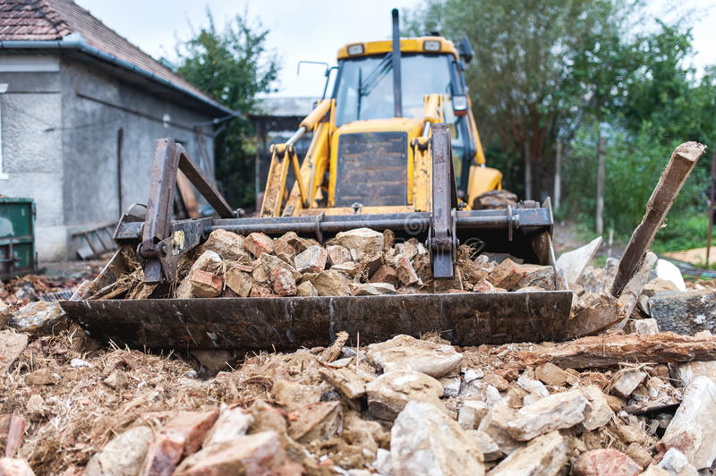 Bulldozer demolishing an old building. And carrying debris royalty free stock photo