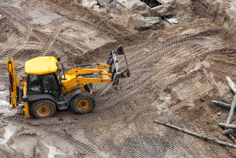 Bulldozer digging the ground. Repair of heating, bulldozer digging the ground royalty free stock photography