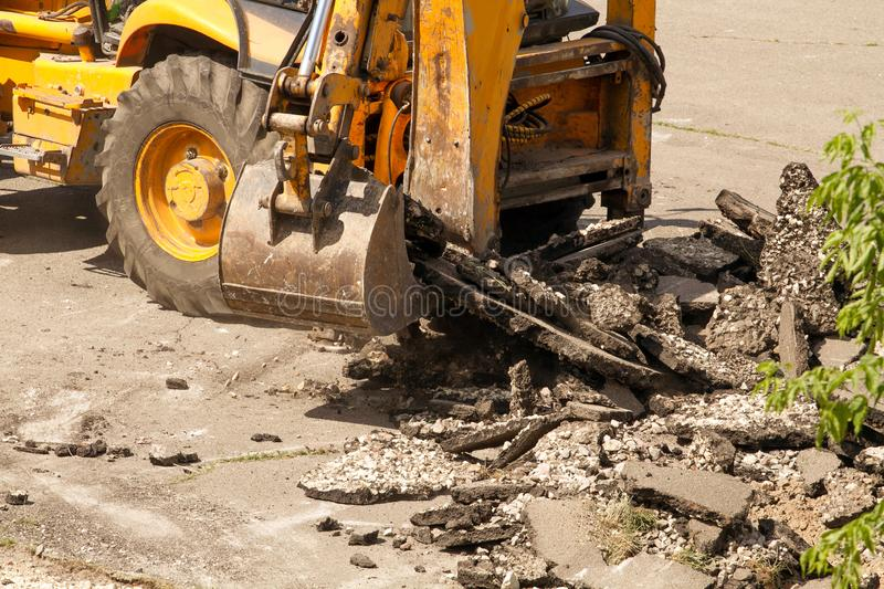 Bulldozer Dismantles Asphalt at Work. Yellow Excavator Dig the Asphalt with Tractor Bucket. Bulldozer Dismantles Asphalt at Work stock photography