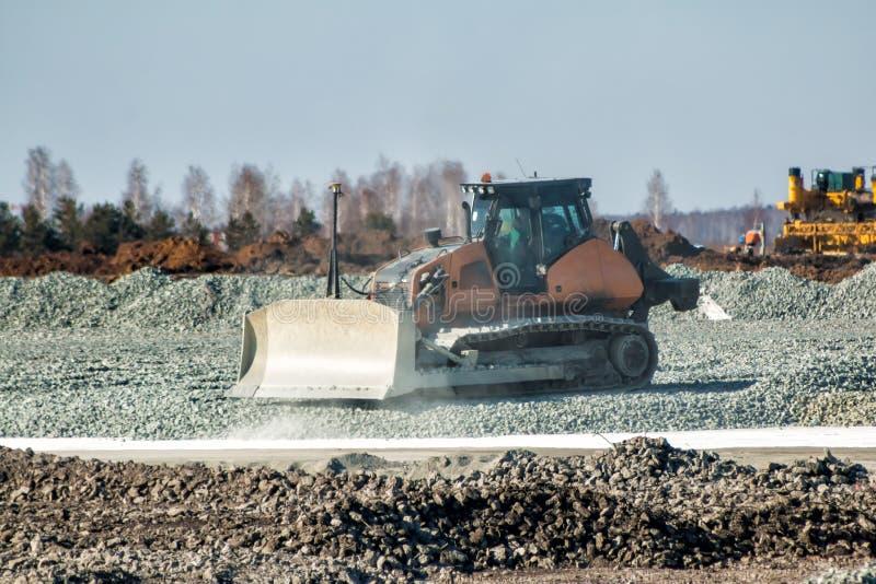 Bulldozer dredges rubble on road construction. Bulldozer dredges ballast on road construction royalty free stock photos