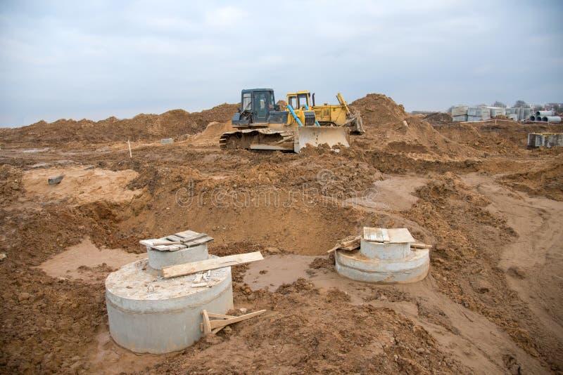 Bulldozer durante la posa di tubi di scarico e di pozzetti di calcestruzzo per l'impianto idrico Collegamento di drenaggio di tri fotografia stock