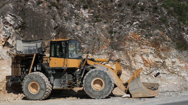 Bulldozer in een marmeren steengroeve van Carrara Groot mechanisch KOMATSU stock afbeelding
