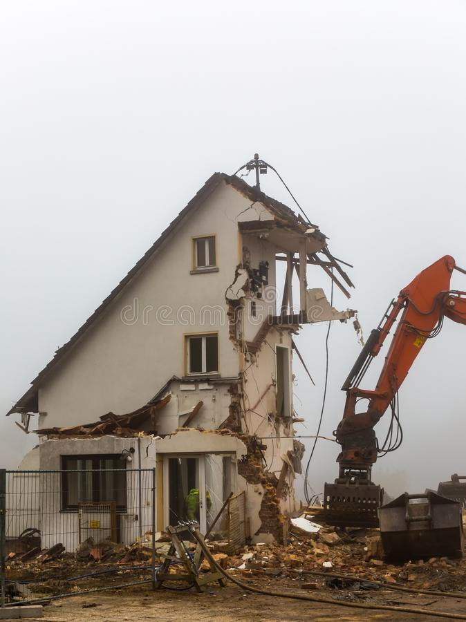 Excavator demolishing old residential building. Bulldozer excavator demolishing old residential building on a foggy day royalty free stock photos