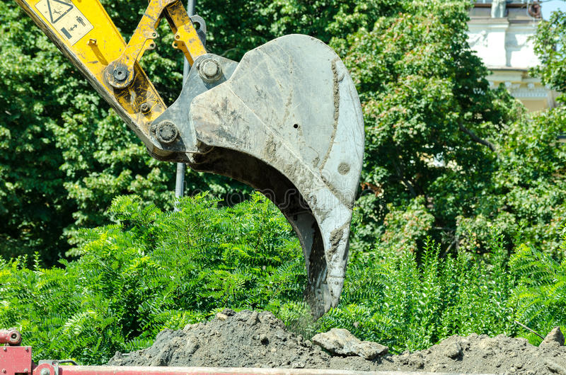Bulldozer excavator loading ground to dumper truck on the construction site. royalty free stock photo