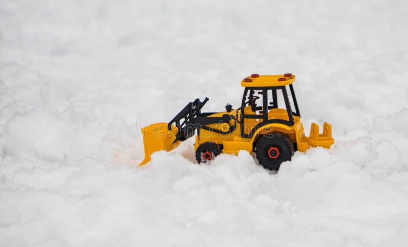 Bulldozer giallo, spazzaneve del giocattolo dell'escavatore disposto nel campo di neve, a fotografie stock libere da diritti