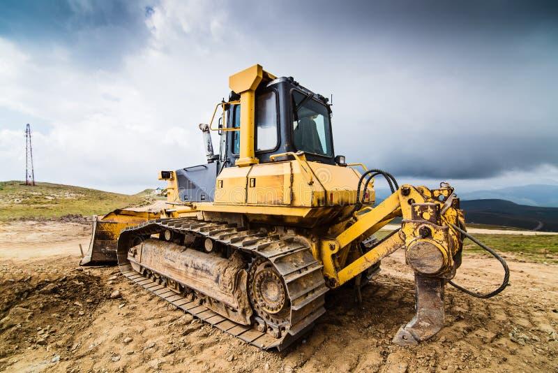 Bulldozer giallo sulle piste fotografia stock