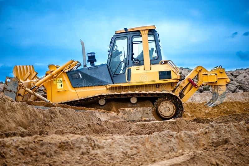Bulldozer of graafwerktuig die met grond aan bouwwerf werken stock fotografie