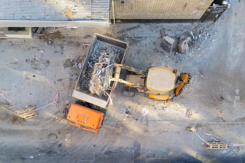 Bulldozer loader uploading waste and debris into dump truck at construction site. building dismantling and construction waste disp. Osal service. Aerial drone royalty free stock photos