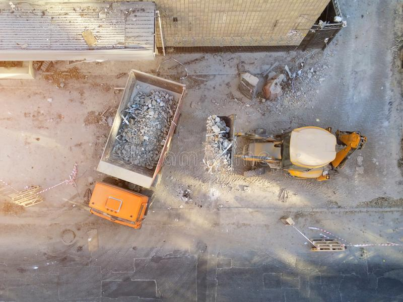 Bulldozer loader uploading waste and debris into dump truck at construction site. building dismantling and construction. Waste disposal service. Aerial drone stock photography