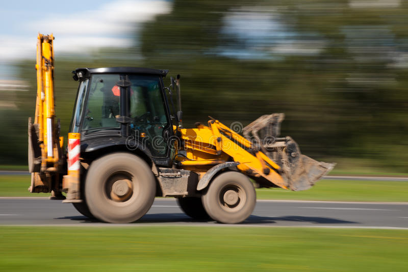 Bulldozer in motion blur. Panning image of bulldozer in intentional blurred motion on a street royalty free stock images