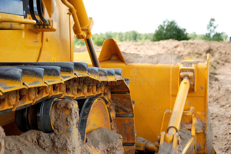 Bulldozer track in action. Close-up buldozer track and blade in ground royalty free stock images