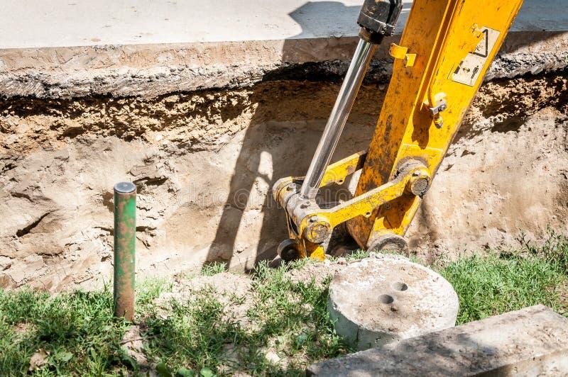 Bulldozergrävskopamaskineri gräver och förbereder sig till att ladda jordning till person som ger drickslastbilen på gatarekonstr arkivfoton