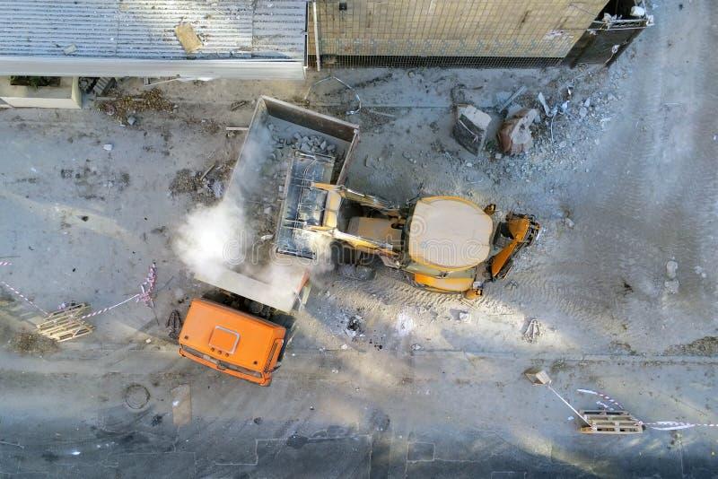 Bulldozerladdare som laddar upp avfalls och skräp in i dumper på konstruktionsplatsen byggnadsdemontering och konstruktion royaltyfri bild