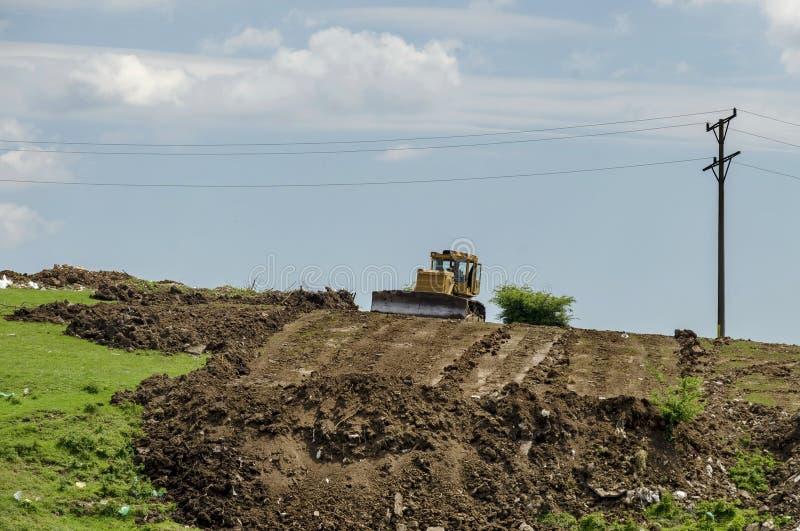 Bulldozern begraver avskräde på rackar ner på förrådsplatsen i fältet royaltyfria foton