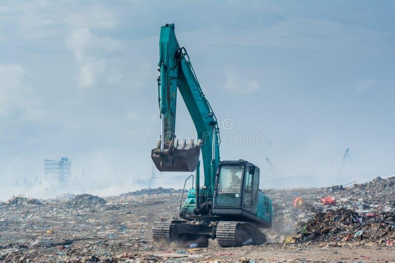 Bulldozern på avskrädeförrådsplatsen mycket av rök, kull, plast-flaskor, rackar ner på och kasserar på den tropiska ön royaltyfria bilder