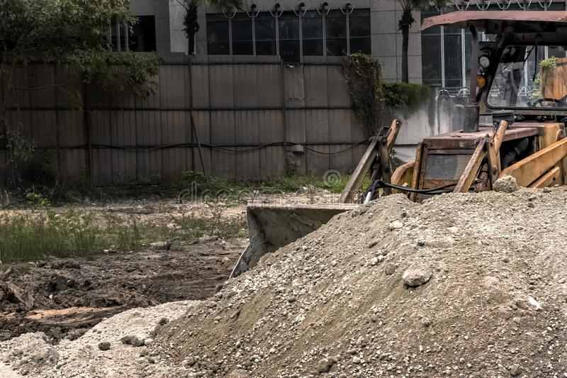 bulldozern på konstruktionsplatsen skyfflar en hög av spillror tonat arkivbild