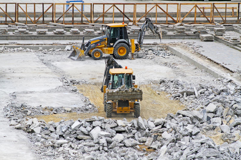 Bulldozers with pneumatic hammers and buckets crush and clear the site of concrete under construction on the Mamaev Kurgan in. Volgograd, Russia - June 24, 2014 royalty free stock photography