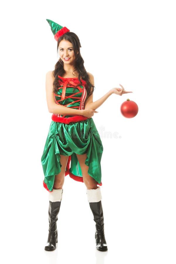 Bulle accrochante de Noël de femme intégrale sur son doigt se tenant à califourchon sur image stock