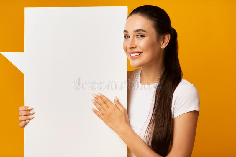 Bulle blanche de la parole de femme de blanc magnifique de participation sur le fond jaune photos stock