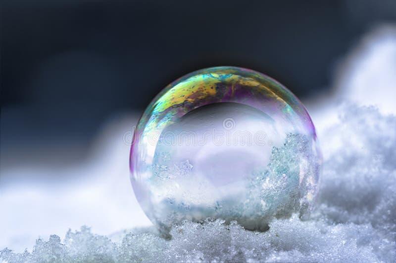 Bulle de savon avec des réflexions d'arc-en-ciel dans la neige, hiver toujours l photo libre de droits