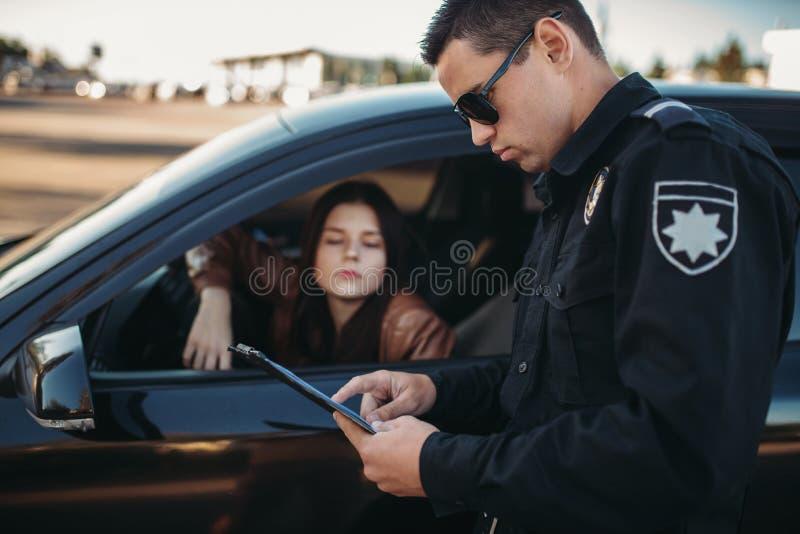 Bulle in der Uniform überprüft Lizenz des weiblichen Fahrers stockfotos