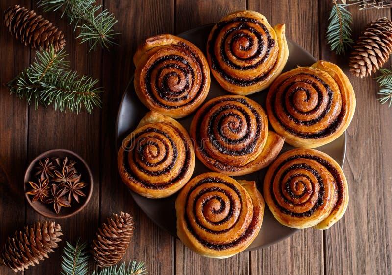 Bullejul för kanelbruna rullar som bakar på en träfrukosttabell Top beskådar Festlig garnering med sörjer kottar royaltyfri bild