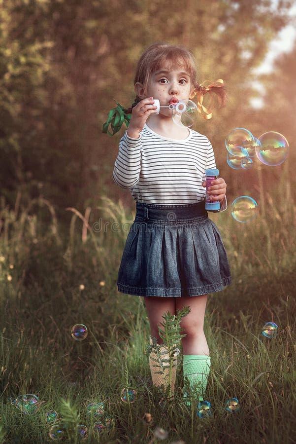 Bulles de coup de petite fille photographie stock