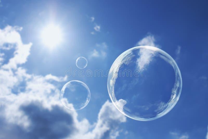 Bulles de savon de flottement contre le ciel bleu et les nuages ensoleillés clairs