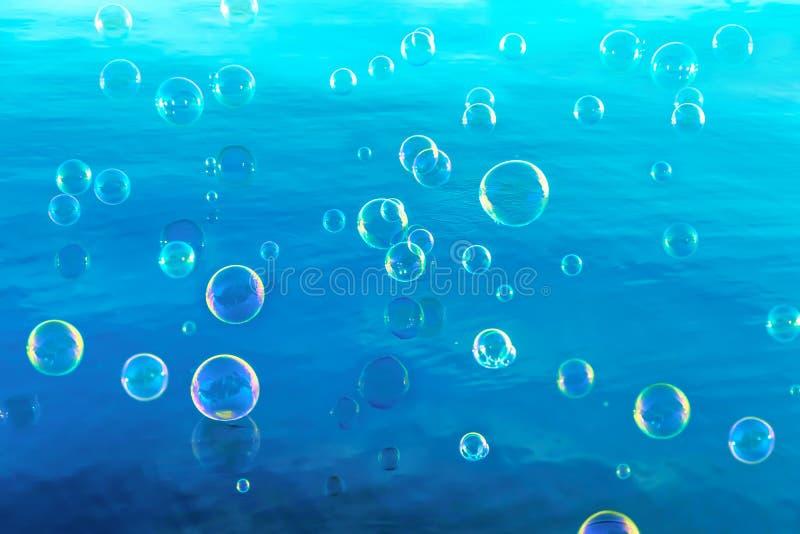 Bulles de savon sur le fond de l'eau bleue photo libre de droits
