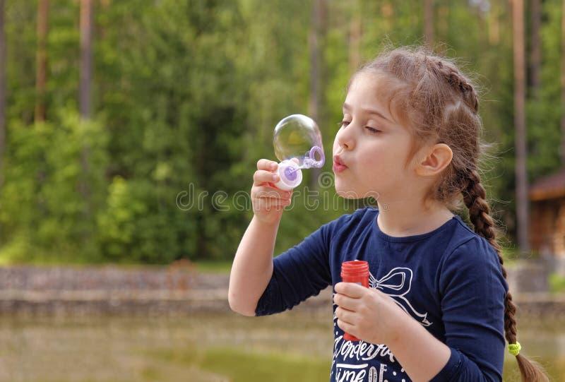 Bulles de soufflement adorables de petite fille en parc images libres de droits