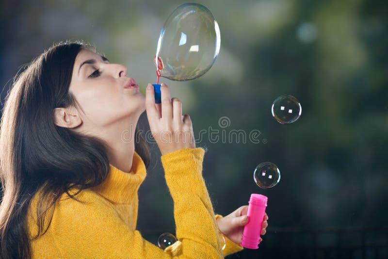 Bulles de soufflement de jeune femme image stock