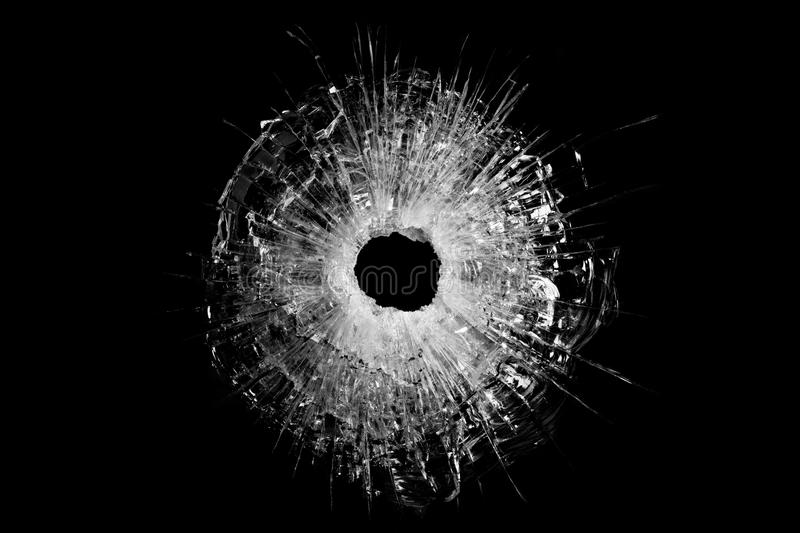 Bullet hole in glass isolated. Bullet hole in glass closeup and isolated on solid black. Actual gunshot from a .44 handgun stock photo