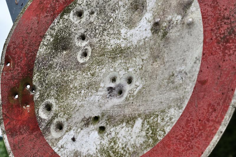 Bullet holes from gun shooting exercises in a german traffic sign stock images